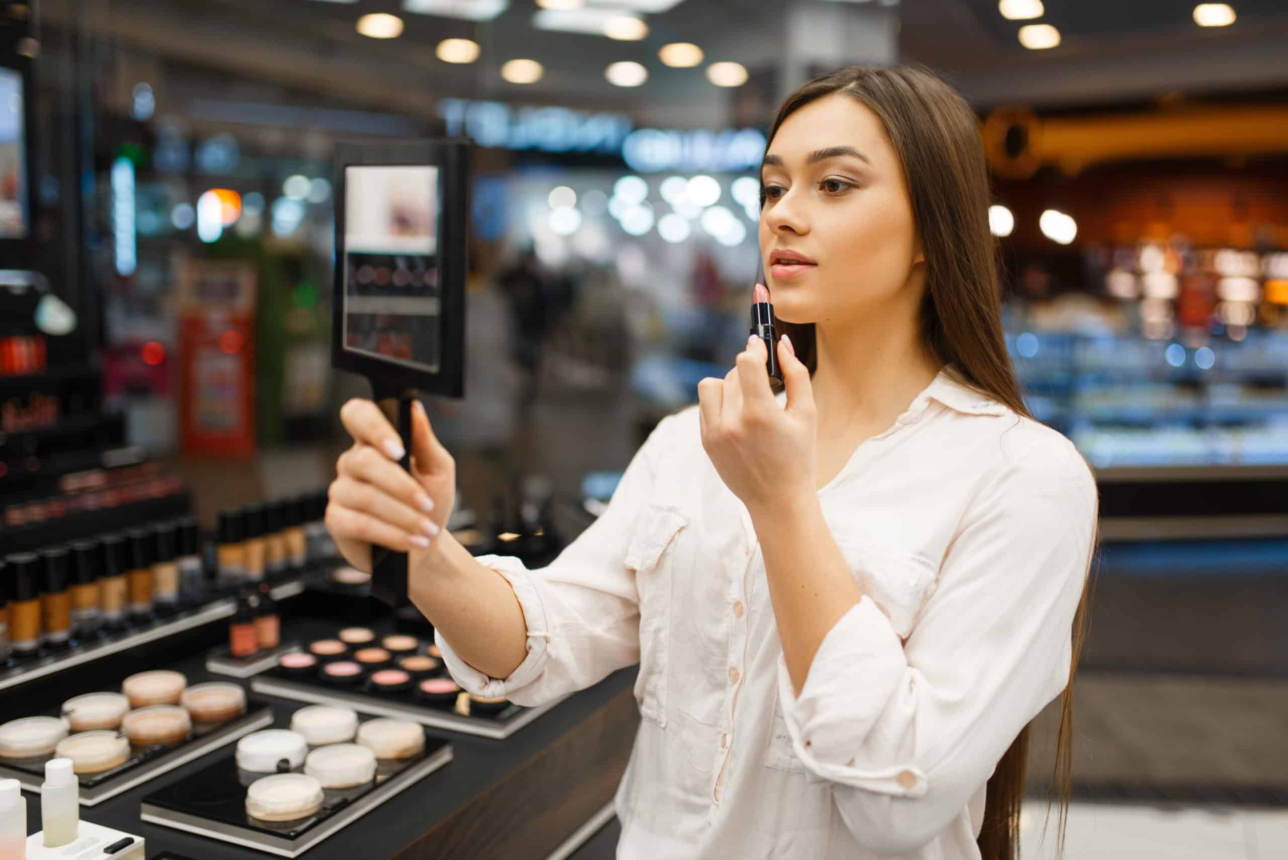 Attractive woman with mirror applies lipstick in cosmetics store. Buyer at the showcase in luxury beauty shop salon, female customer in fashion market