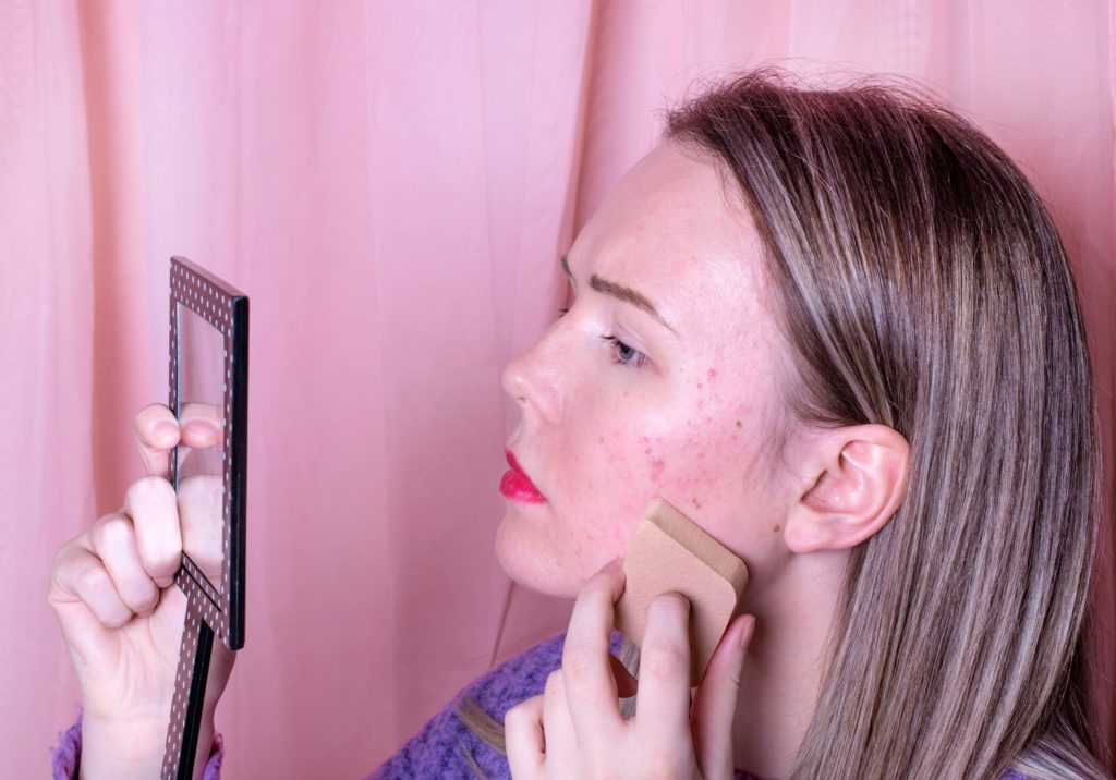 Girl learning how to use makeup to cover acne